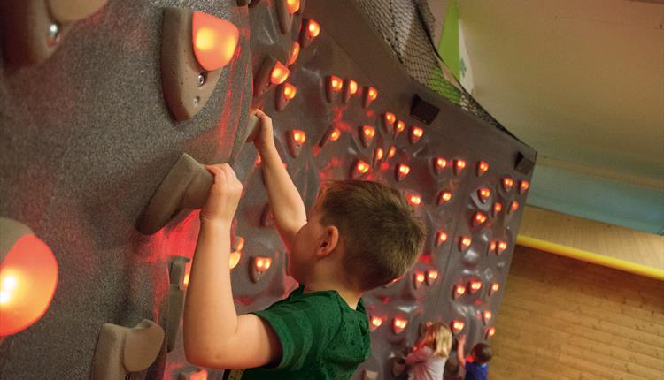 Kid on illuminated climbing wall