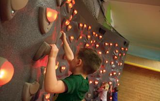 Kid on illuminated climbing wall