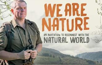 Ray Mears in outdoors gear holding a pair of binoculars