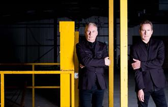 OMD Band Shot, 2 male band members, facing camera with serious expressions, wearing black suits against a dark background