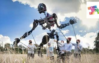 A giant black puppet standing in a wheat field operating by 5 puppeteers in white t-shirts