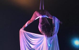 Woman hanging down from the ceiling in white linen wrapped around her