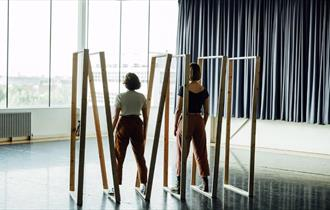 two people dancing in a dance studio looking out to the sea with wooden door frames around them