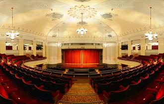 steps down to stage with red curtain closed, red seats in the front and chandeliers dropping from a cream coloured ceiling