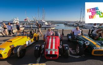 Three sports cars on Poole Quay with boats in background.