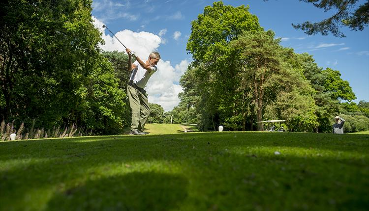 Man winding up his swing before hitting the golf ball on a sunny day
