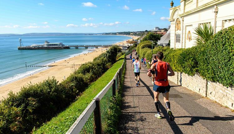 People running down cliff top towards pier with a blue sky