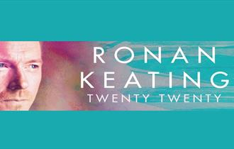 Ronan Keating headshot with blue and purple pastel background.