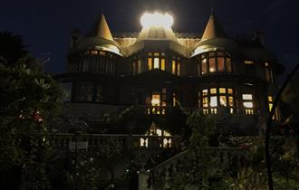A spooky Russel-Cotes house with a dark sky and brightly lit up windows and roof.