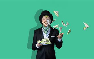 A man in a top hat, throws a plate of cucumber sandwiches in the air, some of which have landed on his face. He is smiling, the background is green.