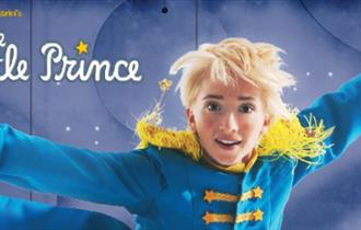 A boy with blonde hair, jumping, wearing a blue jacket with yellow tassels on the shoulder.