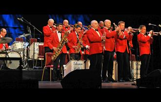 Glenn Miller Orchestra all standing and playing on stage wearing orange - red jackets