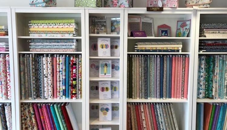 A shelf stocked with craft paraphernalia.