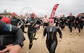 Lady in swim gear running with crowd down the beach