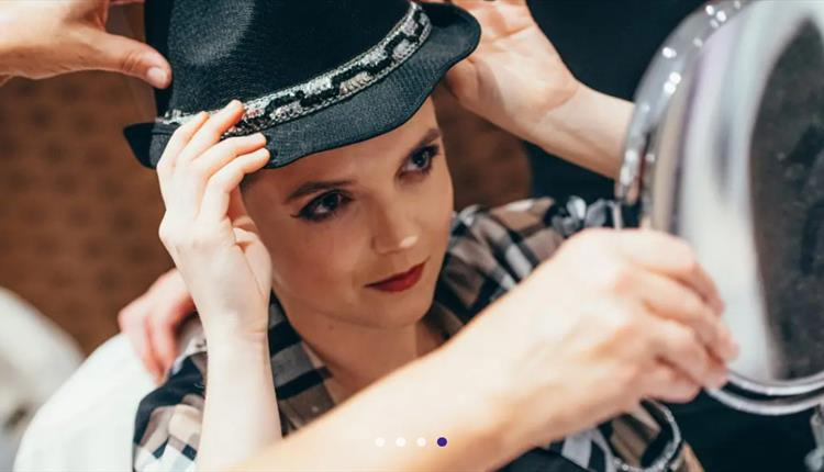 Girl holding a hat looking into the mirror