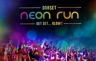 Dorset neon run logo over image of runners with their hands in the air