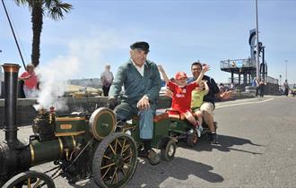A man driving the mini steam on Poole quay with two children and a man riding as passengers