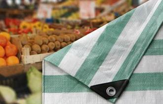 Folded market tarpaulin with fresh fruit and veg in background.