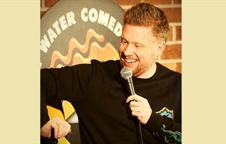 Man speaking into mic, wearing black long sleeved top and looking downwards and smiling while telling a joke