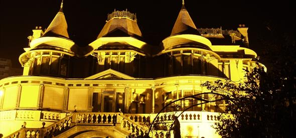 Exterior of Russell-Cotes illuminated at night by orange light