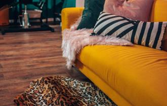 Inside of tattoo studio with yellow sofa and leopard print rug.