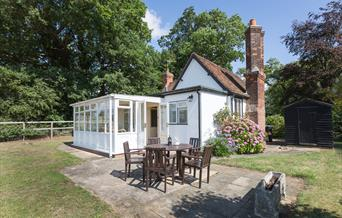 Photograph of South Lodge self catering cottage, white cottage with red roof tiles and white conservatory