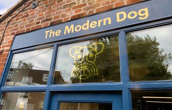 Blue store front with gold dog logo.