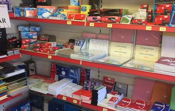 Multiple shelves with many items of stationery including pads files and envelopes