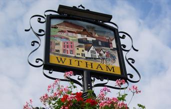 Image of Witham Town Centre sign including flower arrangements