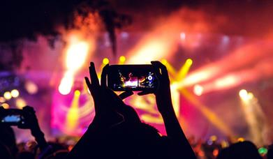 People at a concert taking pictures with phones