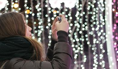 Youngster taking pictures of white string lights