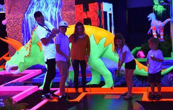 Children playing crazy golf with a fluorescent Triceraptops dinosaur behind them!