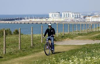 Cyclist on top of cliff with Brighton Marina in background