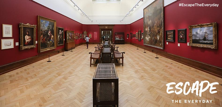 Paintings hang on the red walls of Gallery 3 in Bristol Museum & Art Gallery