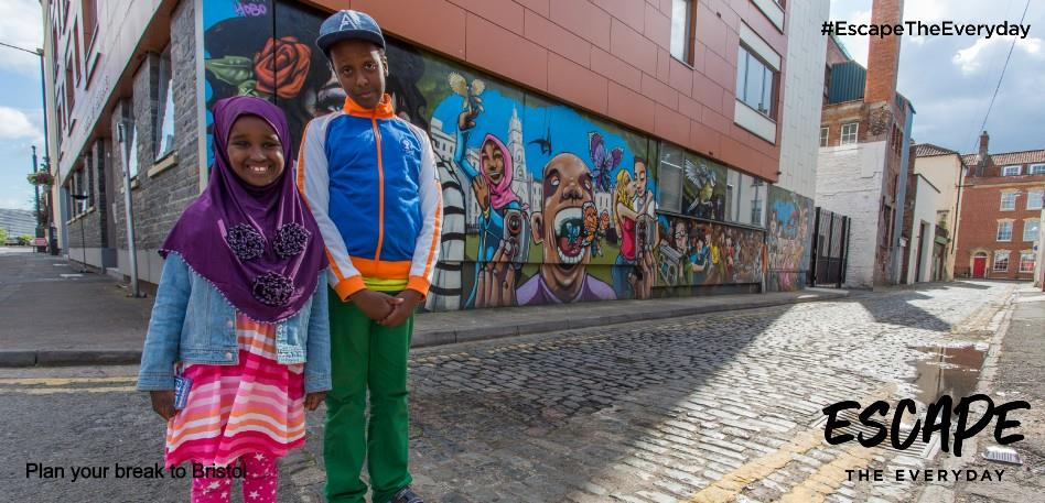 Two children standing in front of colourful street art in Bristol