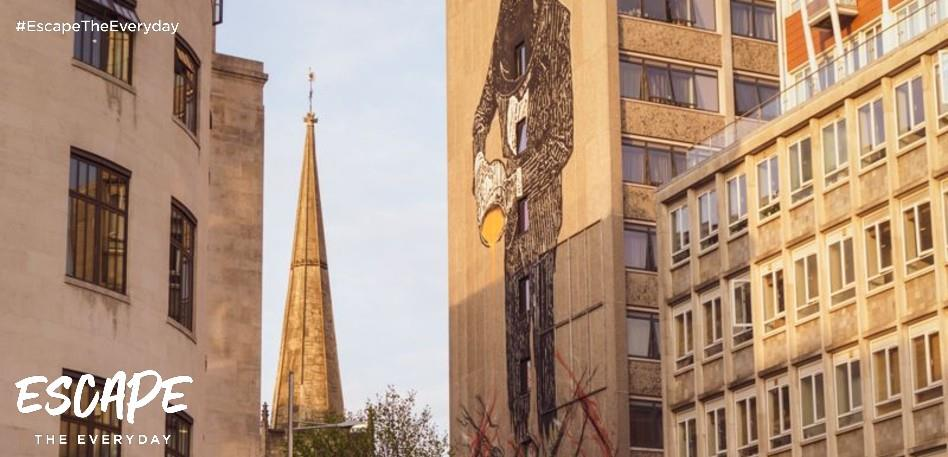 A view of different types of architecture together with street art of suited main pouring paint, a 12-storey high mural by Nick Walker, and a church spire behind.
