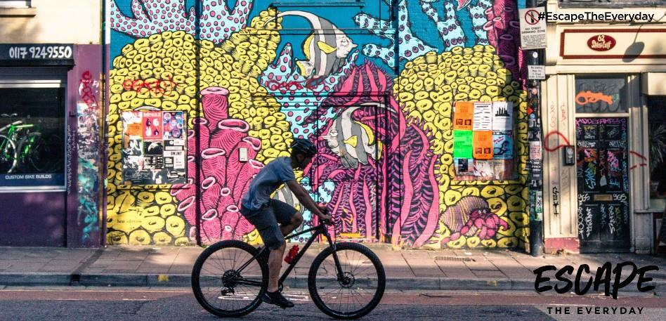 A person riding a bicycle past street art in Stokes Croft in Bristol