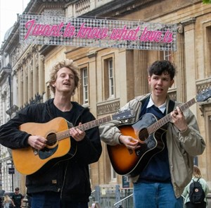 Buskers singing in front of 'I want to know what love is' banner