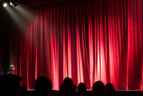People sitting in a theatre in front of a red curtain