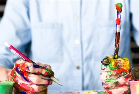 Artist holding a pencil and paintbrush with paint covering their hands