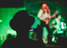 Person recording video of a person playing guitar onstage