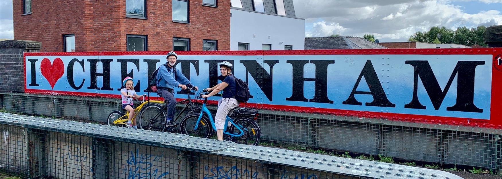 Family on bikes in front of I love Cheltenham street art