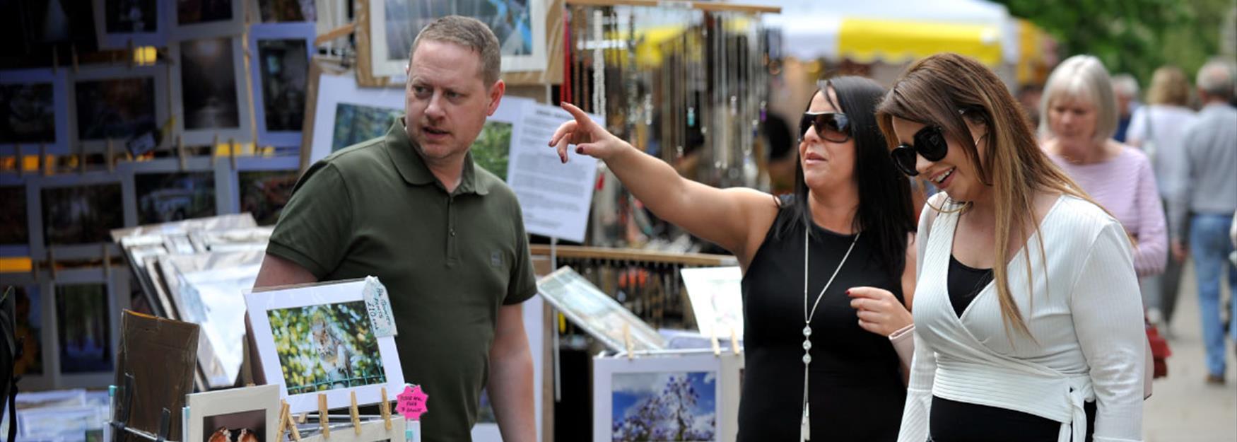 Two women browsing an art stall at a Cheltenham craft market