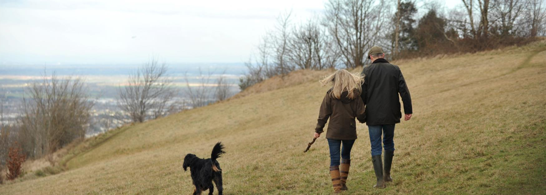 Couple walking their dog in the countryside surrounding Cheltenham