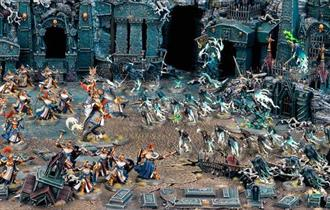 Scene filled with Warhammer models.