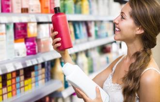 Women taking beauty products off a shelf