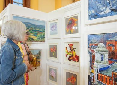 Women looking at paintings at Arts Fair Cheshire