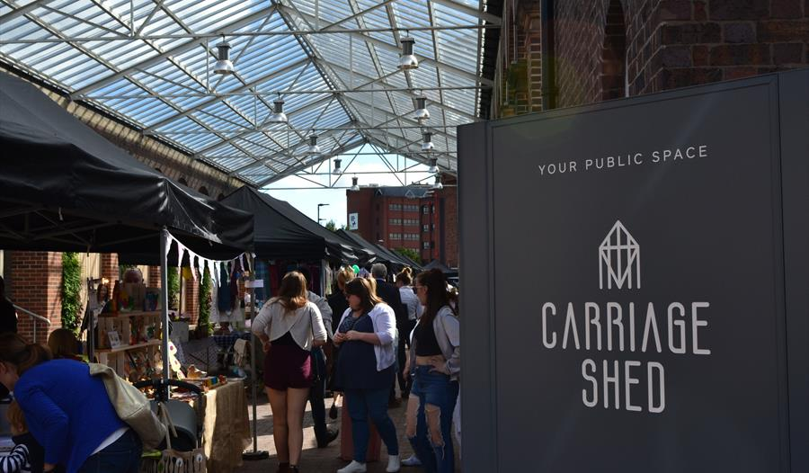 Customers at the Makers Market with the Carriage Shed sign