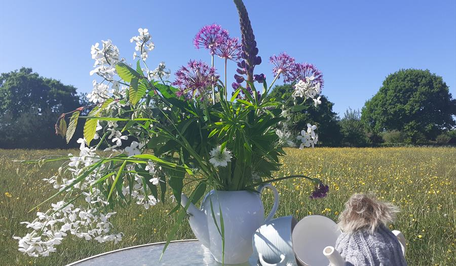 A bouquet of flowers next to a tea pot
