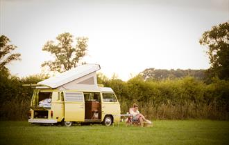 A woman sitting beside a campervan